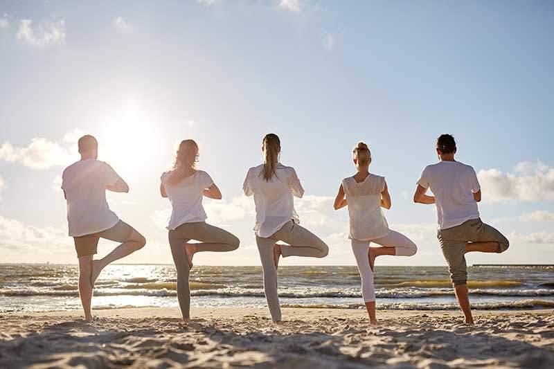 Menschen beim auf Yoga am Strand